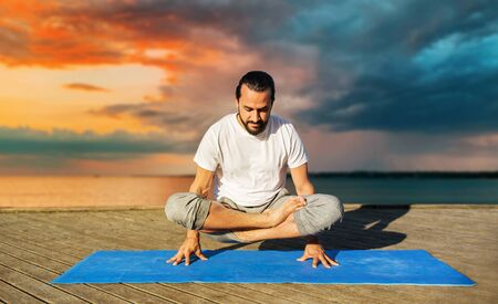 man making yoga in scale pose outdoors 写真素材