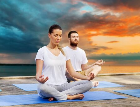 couple meditating in yoga lotus pose outdoors