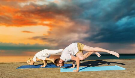 couple making yoga exercises outdoors 写真素材