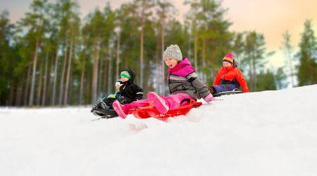 kids sliding on sleds down snow hill in winter Stok Fotoğraf
