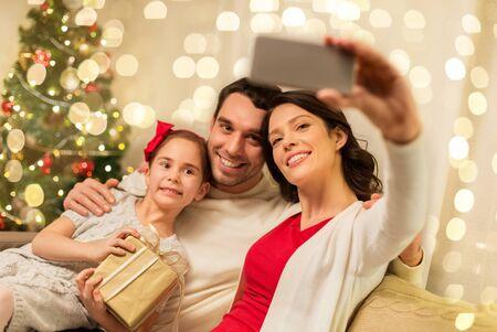 glückliche Familie mit Weihnachtsgeschenk zu Hause