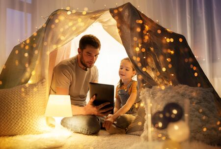 family with tablet pc in kids tent at home Stok Fotoğraf
