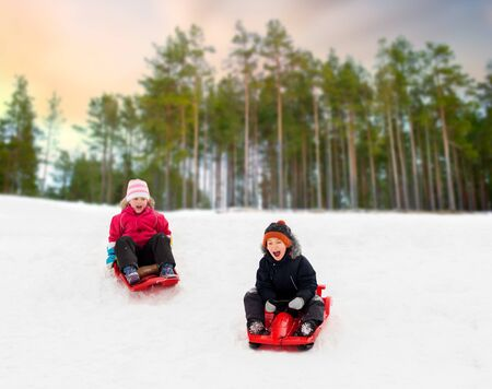 happy kids sliding on sleds down hill in winter