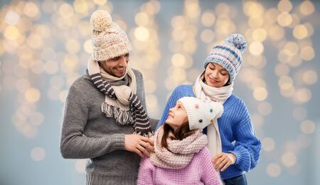 family in winter clothes over christmas lights Stockfoto - 129631459