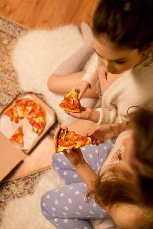 happy female friends eating pizza at home Stock Photo