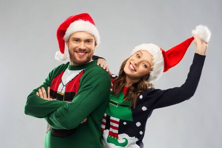happy couple in christmas sweaters and santa hats Stockfoto