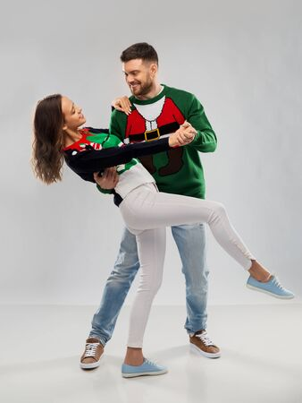 couple dancing at christmas ugly sweater party Stockfoto