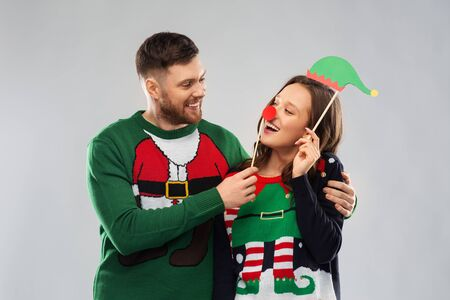couple with christmas party props in ugly sweaters