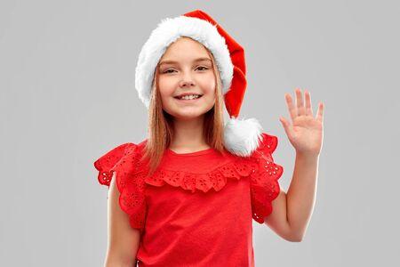 smiling girl in snata helper hat waving hand Stock Photo