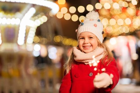 happy girl with sparkler at christmas market 免版税图像 - 129631671