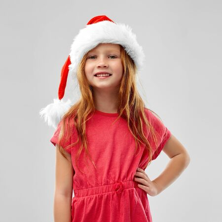 smiling red haired girl posing in snata helper hat