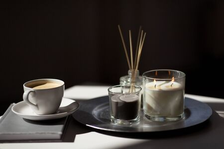 coffee, candles and aroma reed diffuser on table Stock Photo