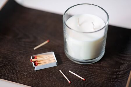 fragrance candle and matches on tray on table