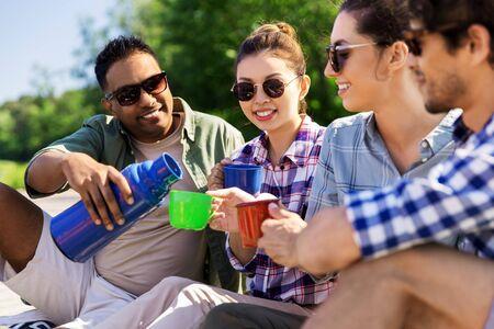 Amigos felices bebiendo té del matraz en verano Foto de archivo