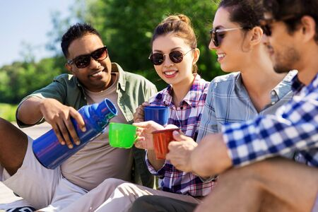 happy friends drinking tea from flask in summer Stock Photo