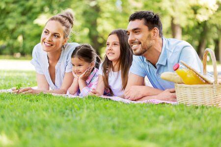 Familia recostada sobre una manta para picnic en el parque de verano