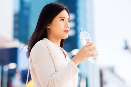 asian woman drinking water from bottle in city 版權商用圖片