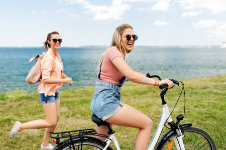 teenage girls or friends with bicycle in summer Imagens