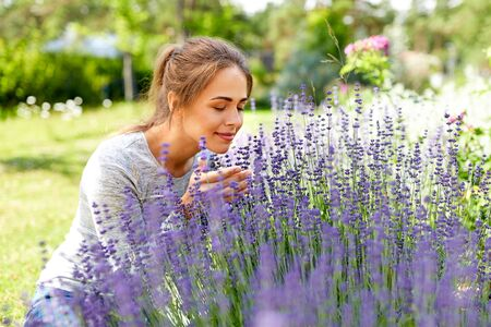 young woman smelling lavender flowers in garden 写真素材 - 129601643