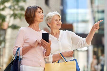 ancianas con bolsas de compras y teléfono celular en la ciudad