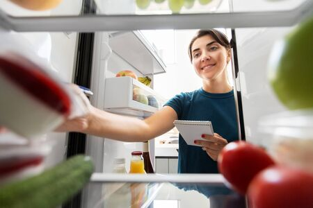 woman making list of necessary food at home fridge Foto de archivo - 129601834