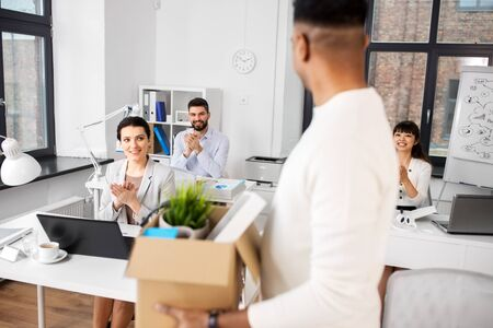 colleagues applauding to male office worker Stock Photo
