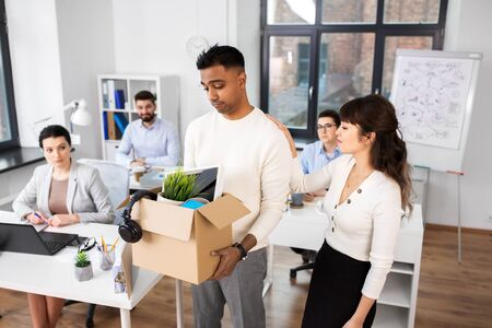 colleague seeing off sad fired male office worker Stock Photo
