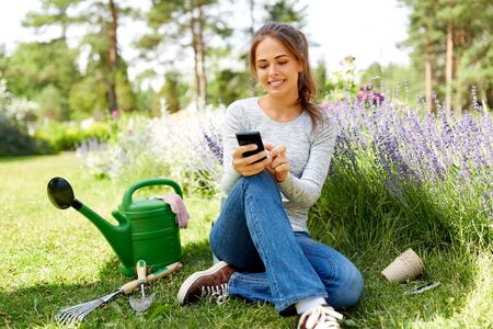 woman with smartphone and garden tools in summer