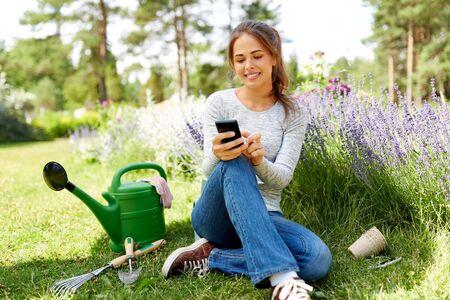 vrouw met smartphone en tuingereedschap in de zomer Stockfoto