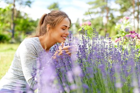 young woman smelling lavender flowers in garden 写真素材 - 129631800