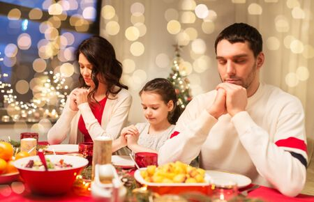 Happy mother, father and little daughter having christmas dinner and praying before meal at home