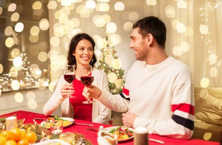 Happy couple having christmas dinner at home and drinking red wine and clinking glasses