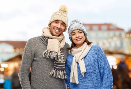 happy couple in winter clothes at christmas market Stockfoto