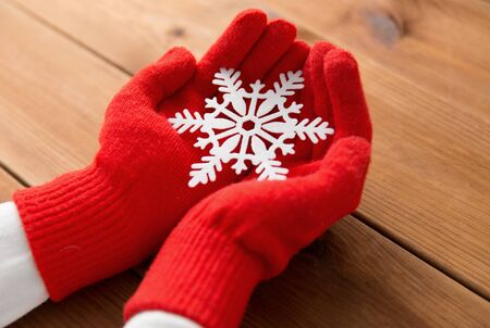Hands in red woollen gloves holding big white snowflake over wooden boards