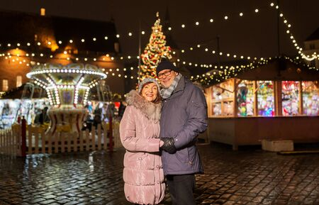 Happy senior couple hugging at christmas market on town hall square