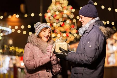 Happy senior couple with gift at christmas market on town hall square
