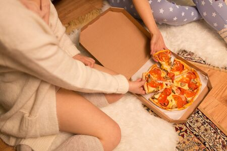 Happy female friends eating takeaway pizza at home