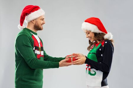 Happy couple in santa hats with christmas gift at ugly sweater party
