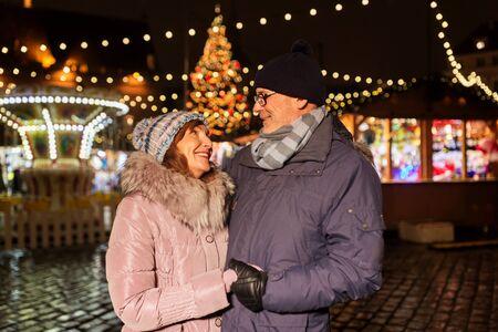 Happy senior couple at christmas market on town hall square in tallinn, estonia