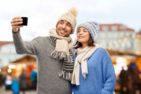 Happy couple in knitted hats and scarves taking selfie by smartphone over christmas market in old town of tallinn city