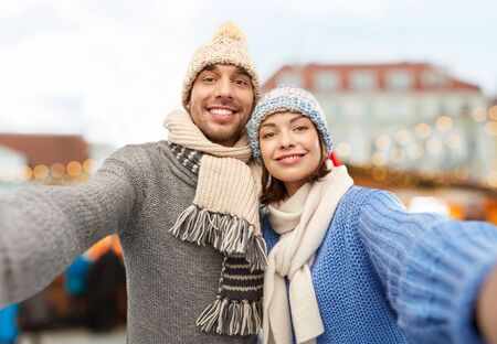Happy couple in knitted hats and scarves taking selfie over christmas market in old town of tallinn city