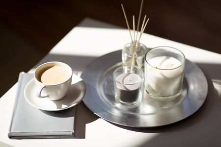 Coffee, candles, book and aroma reed diffuser on table