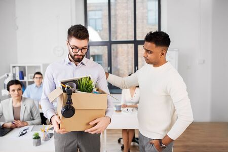 Colleague seeing off sad fired male office worker holding box of his personal stuff