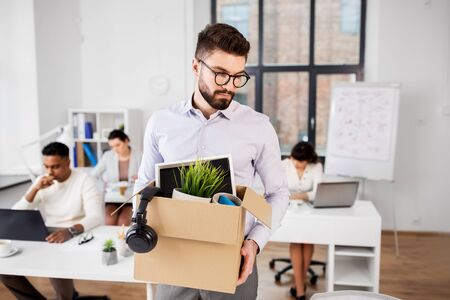 Sad fired male office worker with box of his personal stuff