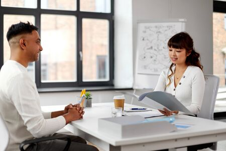 Smiling asian female employer or hr manager with folder having interview with indian male employee at office