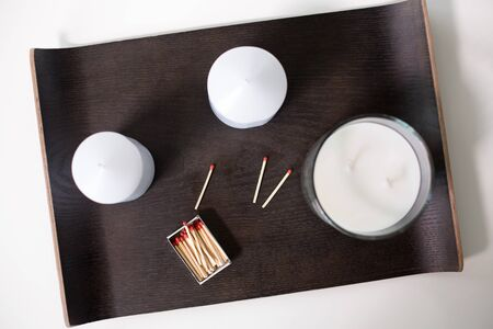 White fragrance candles and matches on tray on table Stock Photo