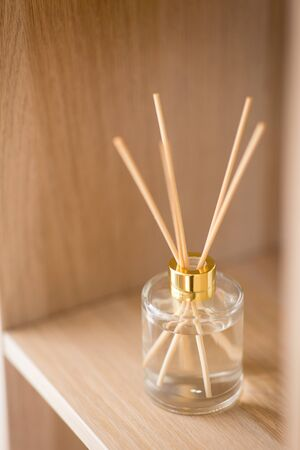Aromatherapy and home perfume concept - aroma reed diffuse on wooden shelf