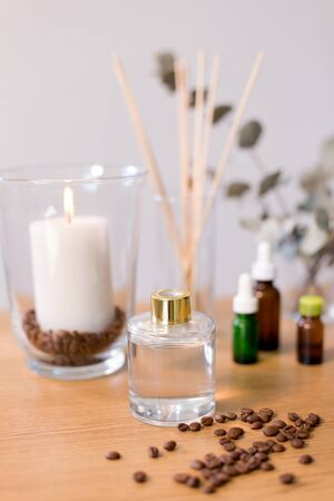 Aroma reed diffuse, burning candle and essential oil on table at home