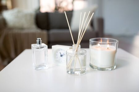Aroma reed diffuse, burning candle and perfume on table at home Stock Photo