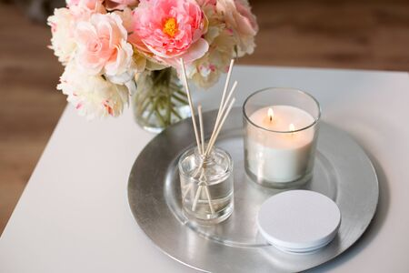 Aroma reed diffuse, burning candle and flower bunch on wooden table 版權商用圖片